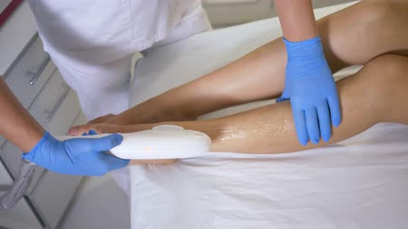 sterilità : unique technologies in cosmetology, beautician does laser photoepilation on feet of patient woman in treatment room of beauty salon, Apparatus for epilation makes flares