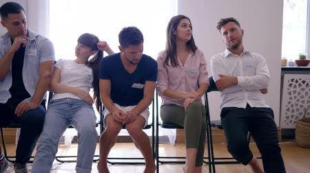 indifference : group of young people with different emotions sitting in row on chairs after therapy meeting