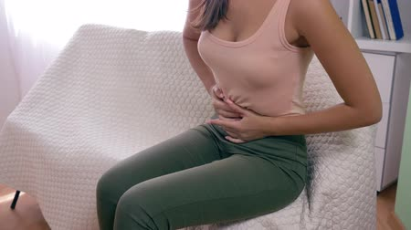 conserva : women pains, girl with strong ache keeps hands on sick abdomen close-up Stock Footage