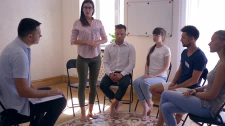 odznaka : group psychotherapy, young woman talking and sharing emotions standing in front of people Wideo