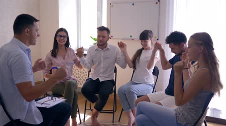 odznaka : happy people hold hands during therapy session at psychologist sitting on chairs in circle