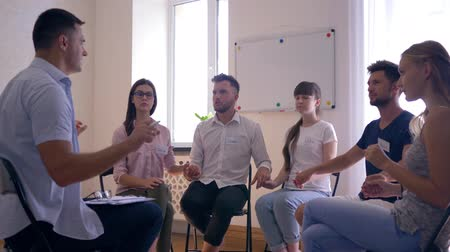 psychotherapist : people meditating with eyes closed sitting on chairs during therapy session at psychologist Stock Footage