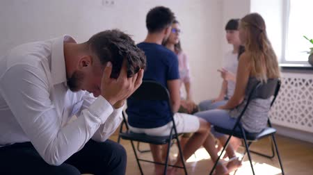 odznaka : sad man crying and covers face with hands on group therapy session on background of people sitting on chairs in a circle