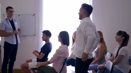 potencial : successful people at training, speaker listens to young guy colleague about development of business ideas in a bright room