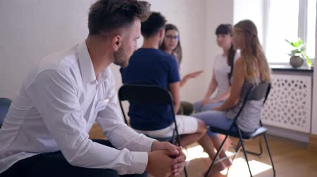 odznaka : unhappy man thinks about the problems on group therapy session on background of people sitting on chairs in a circle
