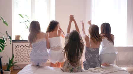 slumber : beautiful female legs closeup, happy girlfriends in pajamas fall on the bed together during the hen party