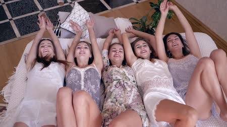 めんどり : happy female friends in sleepwears joyfully fall on the bed and looking at the camera during the hen party at home