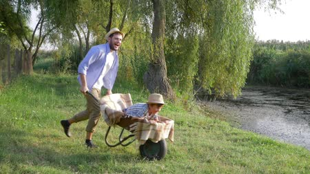 fool : happy childhood, best daddy fun to ride his child boy in a wheelbarrow at countryside