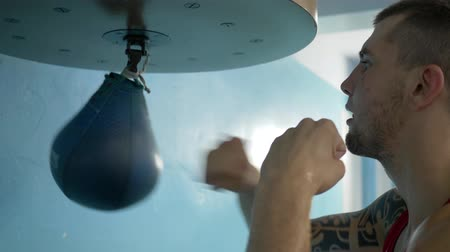 zapasy : KHERSON, UKRAINE - SEPTEMBER 3, 2018: pugilist male practice beats fists on punching bag and trains arm muscles before competition at sports center close-up Wideo