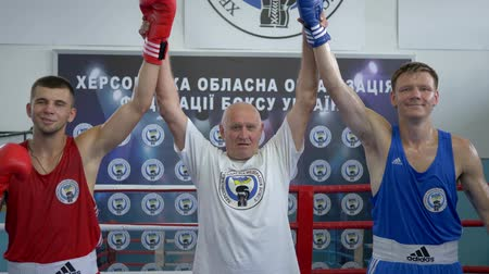 contestant : KHERSON, UKRAINE - SEPTEMBER 3, 2018: victory in boxing competition, referee raises hands of champions after fight on ring