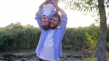idílio : family have fun in countryside, father is holding his son upside down and fooling around on background of nature