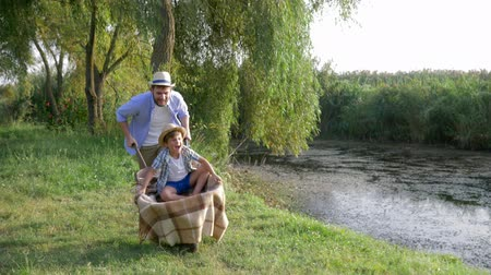 carriola : family vacation in countryside, merry father fool around with his son in a wheelbarrow near small river