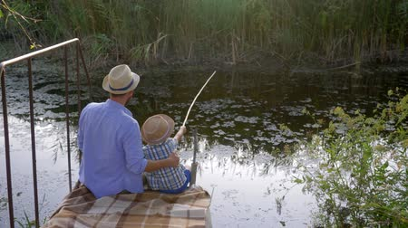 vader en zoon : father and son fishing together on a small river, happy family recreation during vacation