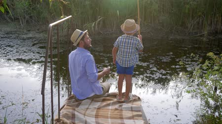 idílio : fishing family, father enjoying time with his young son as he catches his first fish during the holidays Vídeos