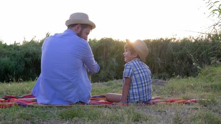 idílio : father son relationship, dad with little boy in straw hats enjoy the sunset sitting on a blanket in the open air Vídeos