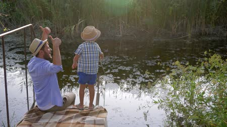 フィッシャー : fishing, dad teaching his son how to fish during family recreation on a small river 動画素材