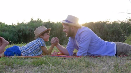 idílio : happy father and son kid play together in arm wrestling lying on the plaid outdoors on background of sunset in rural