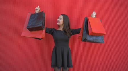 rejoices : black Friday, portrait of happy customer girl with purchases into shopping bags during sales season on background red wall