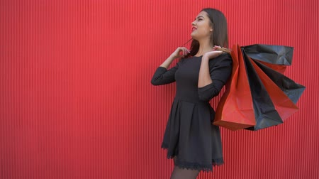 rejoices : happy purchases, reflective woman with many shopping bags thinks what to buy at discount on black friday on background red wall Stock Footage