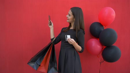 pátek : internet purchases, happy smiling girl makes online shopping using mobile phone and electronic money in black Friday seasonal sale on background red wall