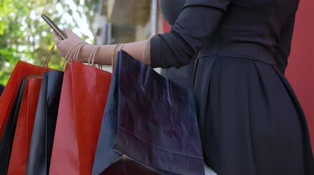 ayrılmak : online purchases, shopper girl uses mobile phone for buying and paying in internet at seasonal sale close up, many shopping bags hanging on hand Stok Video