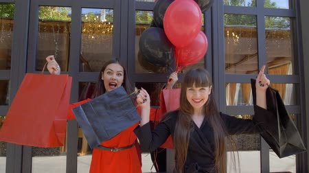 rejoices : shopping day, merry female friends waving bags with new purchases from fashion shop in sale at black friday Stock Footage