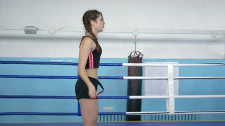 athletes foot : fitness girl does cardio workout with jump rope on boxing ring in sports Complex