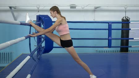 construção muscular : gymnast girl with flexible legs make stretching during workout before competition in sports studio