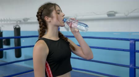 закалки : sports girl drinking refreshing water from plastic bottle for quenching thirst during workout in ring at sports club Стоковые видеозаписи