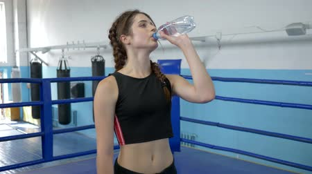 закалки : thirst quenching, tired athletic woman drinking mineral water during sport training in ring indoors