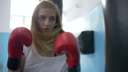punching bag : boxer training in sports club, athletic girl wearing red gloves beating a punching bag close up