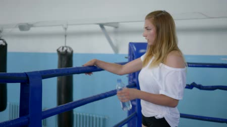 закалки : healthy girl resting after a hard training and drinking water standing on the boxing ring in gym Стоковые видеозаписи