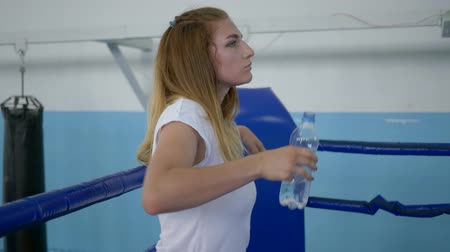 закалки : thirsty sportswoman drinking water from a bottle after a hard workout on the boxing ring