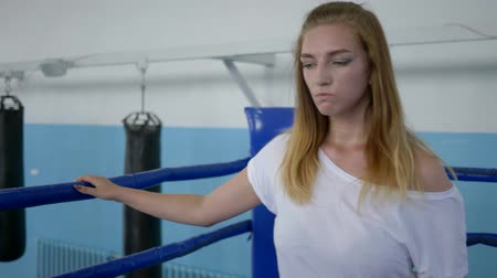 закалки : tired sportswoman drinking water from a bottle after a hard workout on the boxing ring
