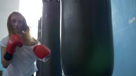 punching bag : young sportswoman wearing gloves in the boxing hall beating a punching bag