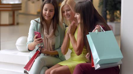 péntek : fashion day, attractive shopaholics women record video on smartphone while shopping with packages in hands during sales season and discounts on black friday in mall