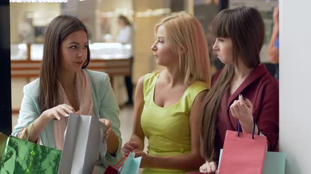 péntek : happy girlfriends at shopping discuss new purchases in packages from expensive boutiques in season of sales and discounts on Black Friday