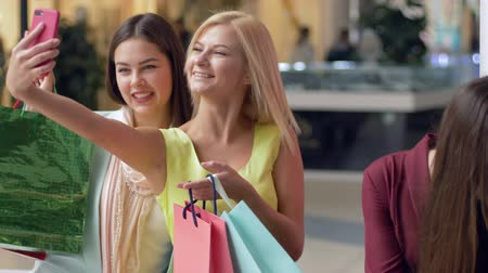 freitag : shopaholics woman friends are photographed on a mobile phone with shopping bags after buy in expensive fashion boutiques in black Friday sales and discounts season Videos
