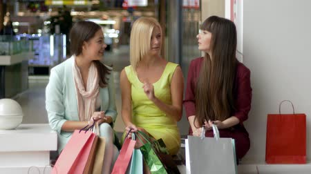 tartışıyor : black friday, ladies having fun discuss their purchases together while sitting at the mall and then look at the camera and smiling with paper bags Stok Video