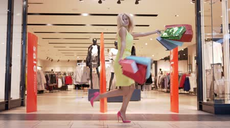 high heeled shoe : cheerful shopping girl dancing in high heels with multicolored packages near shop window in a mall