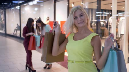 去る : portrait of happy shopping girl in yellow dress with paper bags stands on background of two girls with purchases near shop window in mall 動画素材