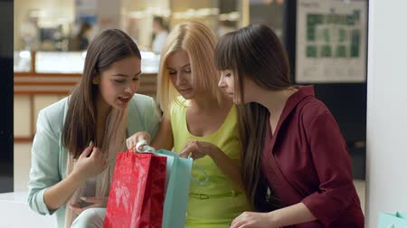 péntek : shopper girls in colorful clothes are considering their purchases in packages after shopping day