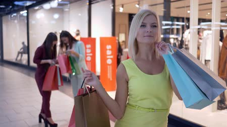 оставлять : shopping girl in a yellow dress with paper bags stands on background of two girls with purchases in mall