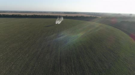 field survey : vintage propeller plane in sunny sky flies over green field with wheat and splashing chemicals against pests into agriculture in drone view