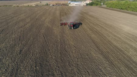 tillage : farm tractor with plough cultivates agrarian land on field before sowing agricultural crops, drone view Stock Footage