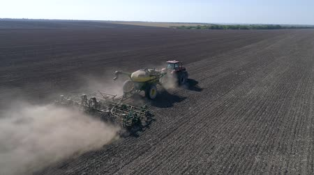 field survey : sowing Grain field, tractor with seeder and plow seed grain in soil at planting season at autumn in drone view