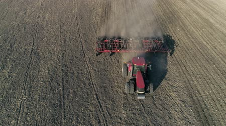 трактор : tillage, farm tractor with plow cultivates soil on field before seeding agricultural crops, drone view