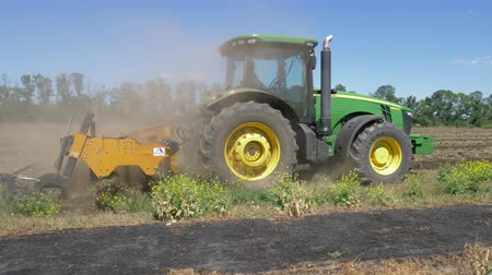 arado : KHERSON, UKRAINE - OCTOBER 01, 2018: tractor with plow cultivates soil in field and lot of dust close-up against blue sky Stock Footage