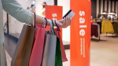 beaucoup d argent : internet shopping, credit card in hands of women with lot purchases bags close-up in season of discounts and sales