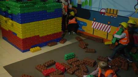 puericultura : KIEV, UKRAINE - OCTOBER 18, 2018: profession of children, kids in safety helmets at construction site build a building with the constructor